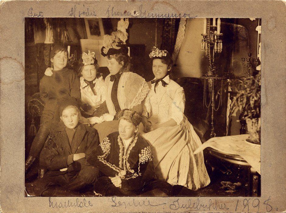 """Julebukkene (bak fra venstre) Augusta Bonnevi, Hjordis Fosterud, Thora Høyer, Minnemor Chritensen, (foran fra venstre) Mathias Olsen og Sophie Eyde fotografert i 1898. Ungdomene har kledd seg ut som """"Julebukker"""".  Bildet tilhører Eyde-samlingen."""