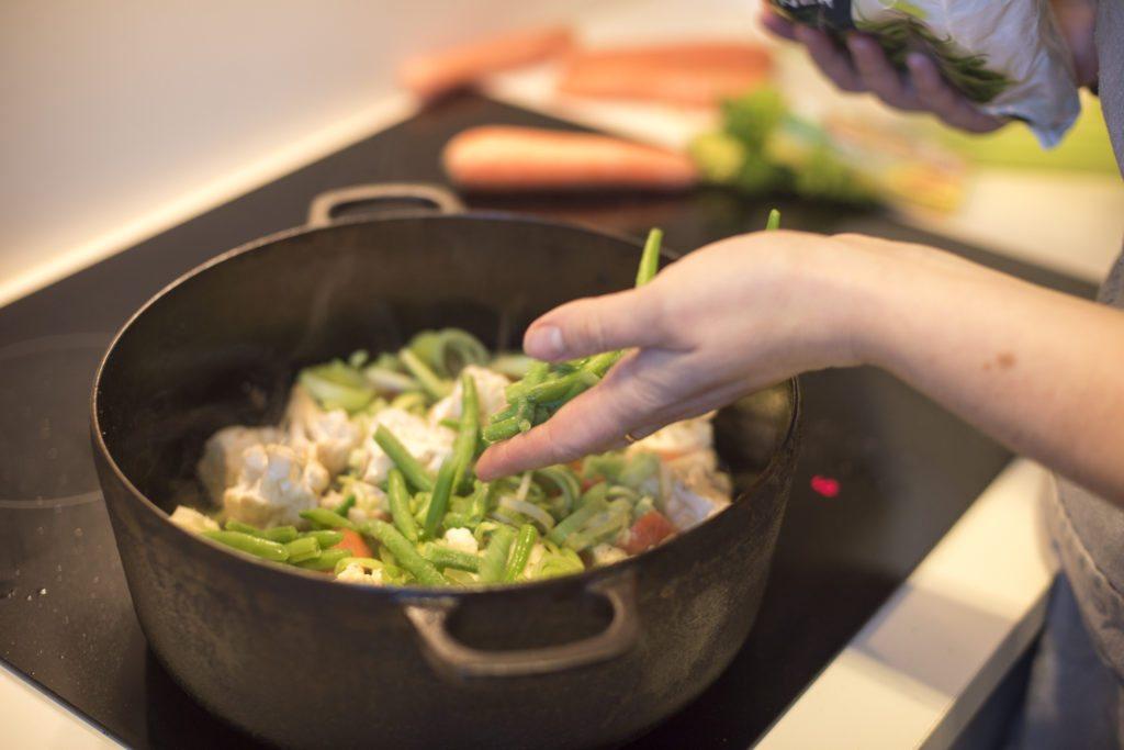 Grønnsaker legges i jerngryten for å kokes