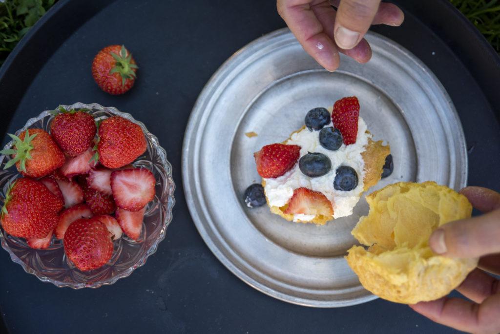 Vi delte vannbakkelsene i to og fylte de med pisket krem og bær